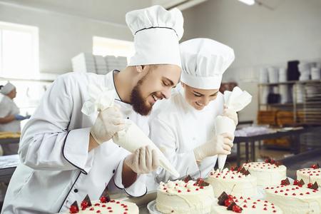 Ein Konditor presst flüssige Sahne aus einem Spritzbeutel in Süßwaren. In der Bäckerei arbeiten zwei Konditoren.