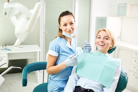 Zahnarzt und geduldiges Mädchen lächeln in der Zahnarztpraxis. Standard-Bild