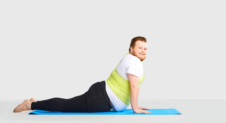 A funny fat man with a beard does yoga exercises on a mat on a background in a studio.