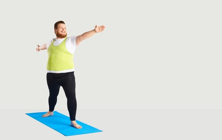 Fat funny man doing yoga on a gray background for text.