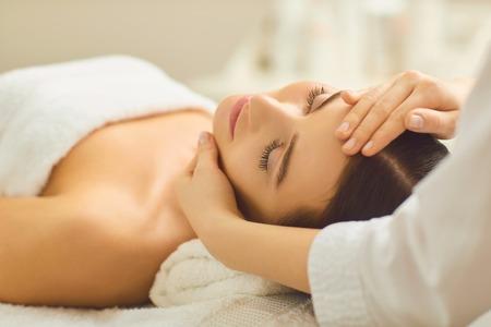 Spa-behandeling bij schoonheidssalon. Een jonge vrouw krijgt een gezichtsmassage in het cosmetologiecentrum. Stockfoto