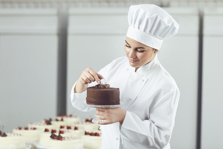 Confectioner woman decorating chocolate cake in pastry shop. 写真素材