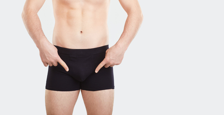A man in black underwear points his finger at the penis. The concept of intimate problems. Standard-Bild - 122065229