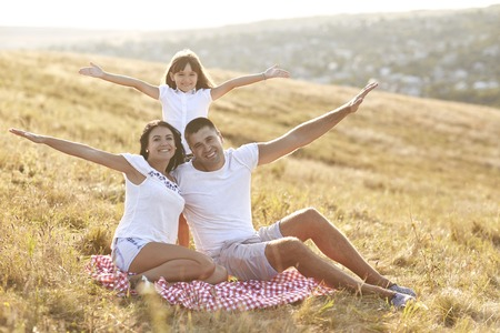 Happy family sitting on the grass on the nature in summer, autumn. Foto de archivo