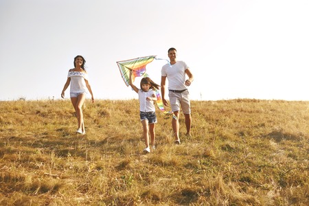 Happy family walking in nature at sunset in summer, autumn.