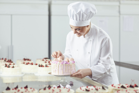 A female confectioner is holding a cake in her hand and in another hand is showing the ok sign in the bakery.