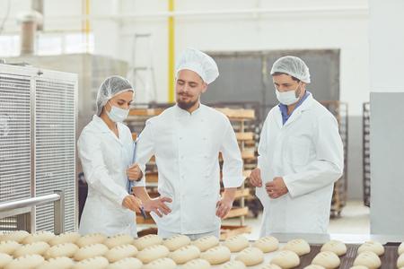 El técnico y el panadero inspeccionan la línea de producción de pan en la panadería.