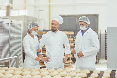 Technologist and baker inspect the bread production line at the bakery. Imagens