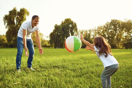 Vader met een kleine dochter spelen met een bal in de lente zomer natuur.