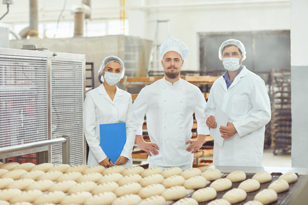 Technologist and baker inspect the bread production line at the bakery. Фото со стока