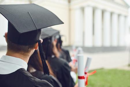 Cap graduate group graduates with scrolls of graduates back view. Graduation.University gesture and people concept.