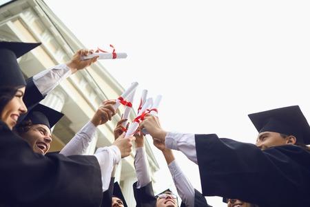 Scorre diplomi nelle mani dei laureati. I laureati sorridono dopo aver ricevuto i diplomi. Graduation.University gesto e concetto di persone.