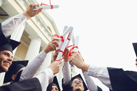 Scrolls diplomas in the hands of graduates. Graduates smile after receiving diplomas. Graduation.University gesture and people concept.