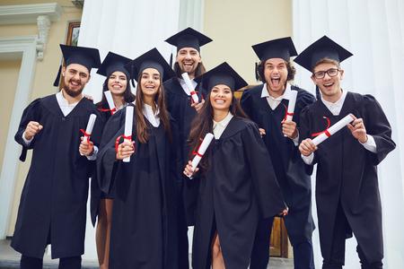 Een groep afgestudeerden met rollen in hun handen lacht tegen de achtergrond van de universiteit. Graduation.University gebaar en mensen concept.