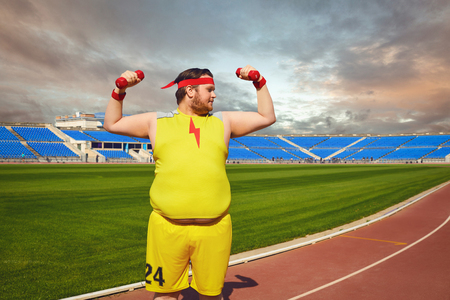 Fat man in yellow sportswear with dumbbells in his hands playing sports at the stadium in the summer. Winner motivation concept. Banco de Imagens - 124898717