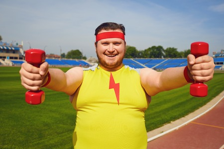 Fat man in yellow sportswear with dumbbells in his hands playing sports at the stadium in the summer. Winner motivation concept.