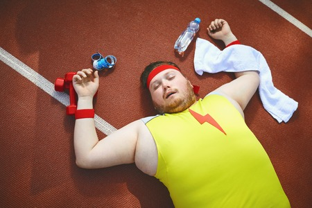 Fat lazy man sleeps tired lies on the track in the stadium. The concept of losing weight, diet. Top view. Banco de Imagens