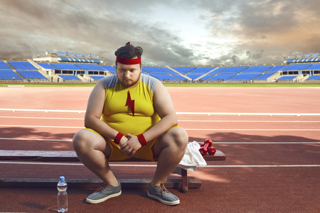 Fat sad man sitting in a stadium after training. The concept of sports, weight loss, diet.