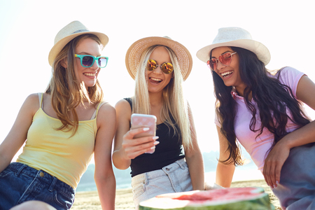 Friends at a party do selfie on the phone on the beach in the park in the summer. Stock Photo