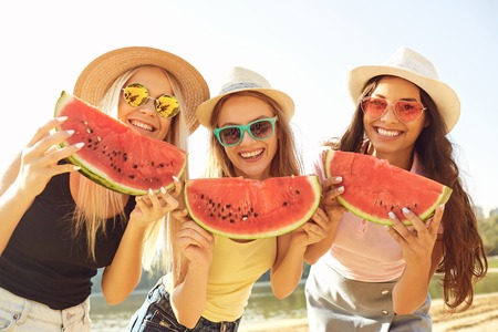 Girlfriends at a party eating a watermelon on the beach in the summer park.