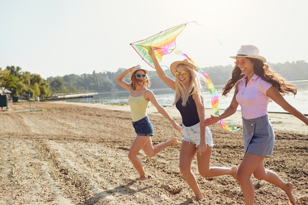 Girlfriends at a party are running with a kite on the beach in the park in the summer.