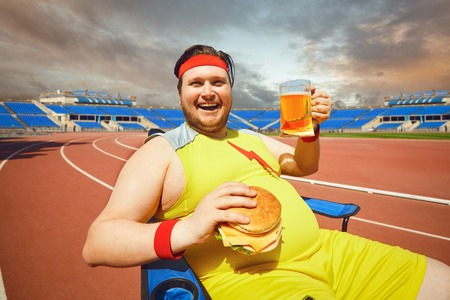 Fat man eating a burger and beer while sitting in training at the stadium. Diet, obesity.