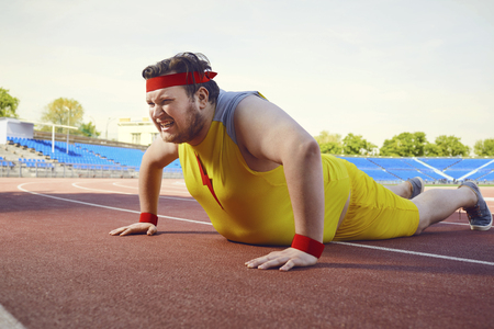 A fat man in sports yellow clothes does push-up exercises at the stadium.