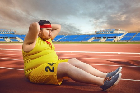 The fat man in sportswear doing abdominal exercises in the stadium in the summer. Winner motivation concept.