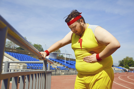 Abdominal pain in a fat man in sportswear in training at the stadium.