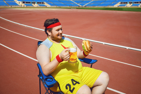 Fat man eating a burger and beer while sitting in training at the stadium. Diet, obesity. Stock Photo - 124898786