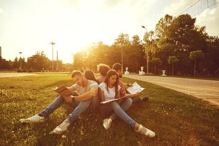 Students study sitting on green grass in a park in summer in spring. Young people with books on the lawn.