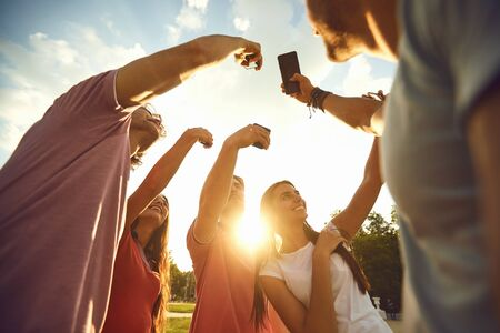 A group of young people raised their hands up with mobile phones on a sunset background. Concept of using mobile phones. 版權商用圖片