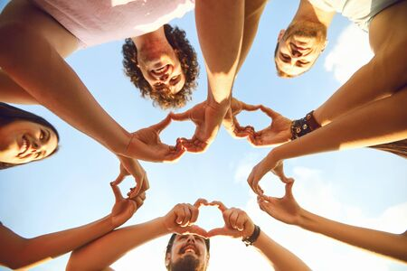 Hands of group people in the shape of a heart against the sky. Love and relationship friendship concept Stock Photo - 124898897