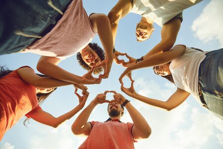 Hands of group people in the shape of a heart against the sky. Love and relationship friendship concept