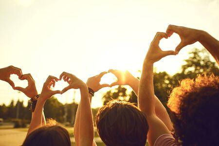 Mains d'amis du groupe en forme de coeur contre le coucher du soleil. Concept d'amitié d'amour et de relation