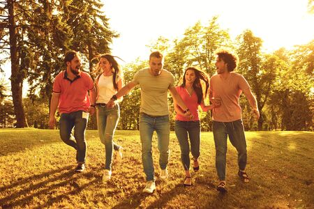 A group of happy young people running at sunset on the nature. Friends in the evening in the park.