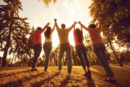 A group of happy young people raised their hands up at sunset on the nature. Friends in the evening in the park. 版權商用圖片
