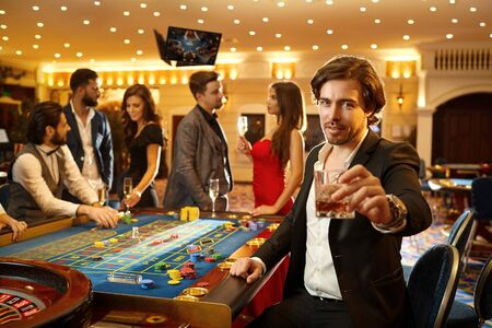 A man in a suit holds a glass with alcohol in his hand against the background of a roulette game in a casino. 스톡 콘텐츠