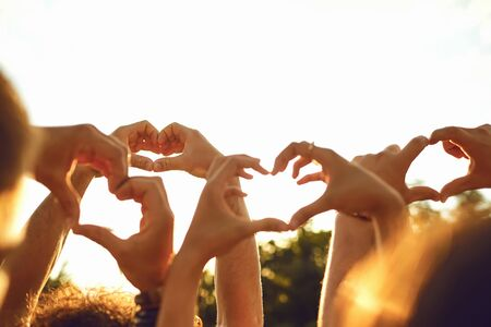 Hands of group people in the shape of a heart against the sunset. Love and relationship friendship concept Stock Photo