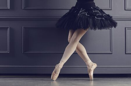 Legs of a ballerina on a black background. The concept of ballet dancing. 스톡 콘텐츠