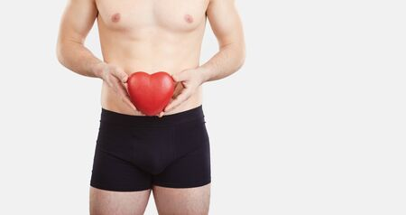 The concept of mens health, sex, lover. A man in black underwear holds a red heart in his hands.