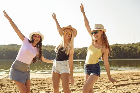 Stylish young women in sunglasses and hats having fun on sandy beach and standing in one pose looking at camera Stock Photo