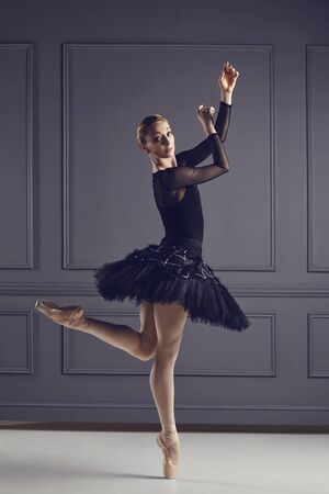 Ballerina in a black tutu posing on a black background. Concept ballet dancing dancer.