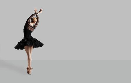 Ballerina ballet dancer in black dress posing over gray background back view. 스톡 콘텐츠