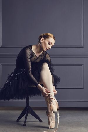 Ballerina in a black tutu sits on a chair on a black background. Concept ballet dancing dancer. 스톡 콘텐츠