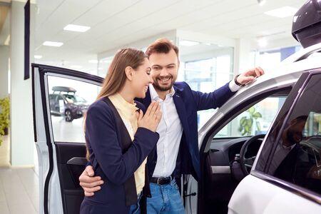 A young couple chooses a car and auto salon. Foto de archivo - 125077724