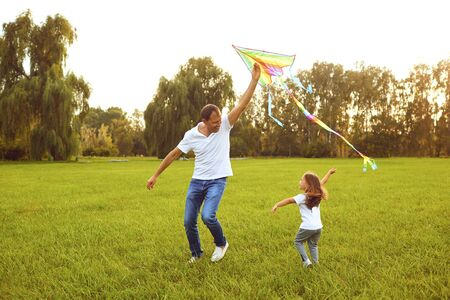 happy family father and child run on meadow with a kite in the summer on the nature