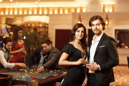 Beautiful glamour couple with glasses of alcohol in hand are standing against the background of casino poker roulette.