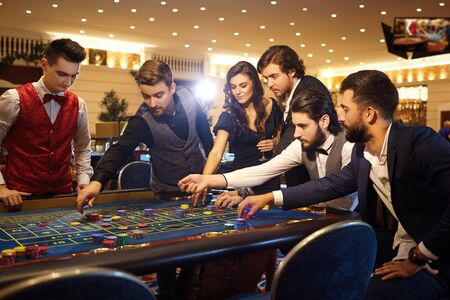 Rich friends make bets gambiling at the roulette table in the casino. Gambling in a casino. 스톡 콘텐츠