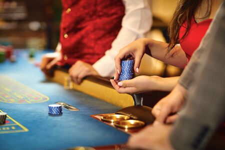 Hands of people with chips at poker roulette table gambling in a casino. 스톡 콘텐츠 - 125337780